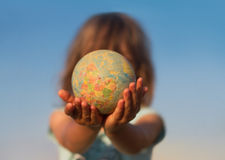 Child hand holding an earth toy globe against a blue sky Stock Photography