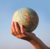 Child hand holding an earth toy globe Royalty Free Stock Photos