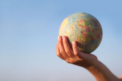 Child hand holding an earth toy globe Stock Photos