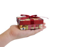 Child hand holding a gift box with red ribbon Stock Photography