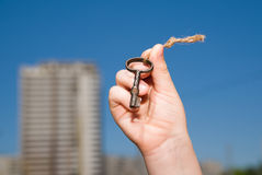Child hand holding an old key on a string Royalty Free Stock Images