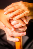 Child hand holding an old womens hand with the cain. Seven year old girl holding her grandmothers hands stock photos