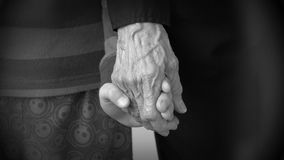 Child hand holding the old wrinkled hand of his grandmother stock footage