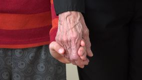 Child hand holding the old wrinkled hand of his grandmother stock video
