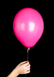 Child hand holding pink balloon isolated on black Royalty Free Stock Photography
