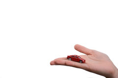 Child hand holding a red car. Child's hand holding a red car on a white background Royalty Free Stock Photography