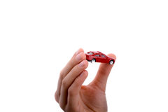 Child hand holding a red car. Child's hand holding a red car on a white background Royalty Free Stock Image