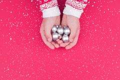 Child hand holding silver christmas baubles royalty free stock photography