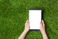 Child hand holding tablet pc. over green grass Royalty Free Stock Photos