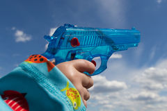 Child hand holding toy gun / water pistol Stock Photo
