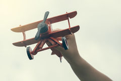 Child hand holding wooden handmade airplane Royalty Free Stock Photo