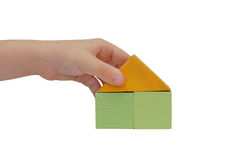 Child hand make a building with colored blocks Stock Photos