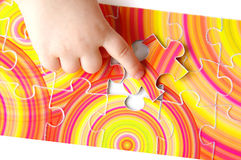 Child hand ond puzzle Royalty Free Stock Photography