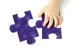 Child hand ond puzzle Royalty Free Stock Images