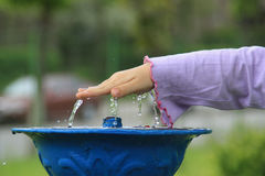Child hand over water. A child hand interrupting an water jet Royalty Free Stock Photography