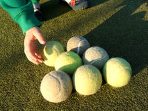 Child hand picking one of seven tennis balls from court. Child hand dressed in green longsleeve picking one of seven tennis balls from court stock photography