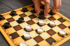 Child hand playing checkers board game. Black and white. Close-up royalty free stock image