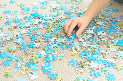 Child hand playing complex puzzle royalty free stock image