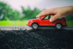 Child hand playing red car there are obstacles blocking the front of the car as a group of screws. Stock Images