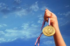 Child hand raised, holding gold medal against sky. education, success, achievement, award and victory concept.