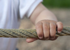 Child hand on rope Stock Photo
