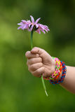 Child hand in rubber band bracelets with flower Royalty Free Stock Image
