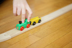 Child hand's playing with a wooden train. Child hand's playing with a wooden toy train stock photo