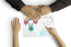 Child hand shows greeting card to dad. Father`s Day. Hands of little child showing a greeting card to his father with heart symbol, handwritten, and family Stock Photos