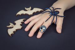 Child hand with skull ring holding a spider royalty free stock images