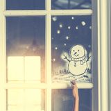Child hand with snowman drawing on window.. Child hand with snowman drawing on window royalty free stock photo