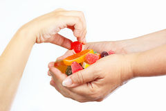 Child hand takes the candy from hands her mother close up Royalty Free Stock Photos
