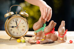 Child hand taking big chocolate bunny beside retro Royalty Free Stock Photo