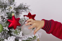 Child hand touching Christmas ornament Royalty Free Stock Images