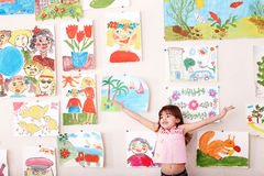 Child with hand up and picture  in playroom. Stock Photo