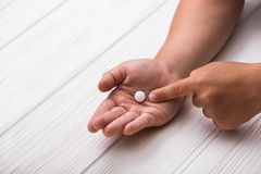 Child hand with white medical pills. On wood background. Children treatment Stock Images
