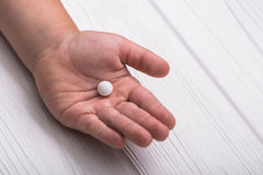 Child hand with white medical pills. On wood background. Children treatment Stock Photo