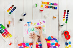 Child hand is writing in album word. Thank you.  Thanksgiving greeting card Royalty Free Stock Photo