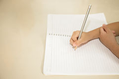 Child hand writing on blank notebook pencil  and copy space in v. Intage tone Stock Image