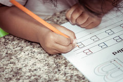 Child hand writing her homework with crayon Royalty Free Stock Photography