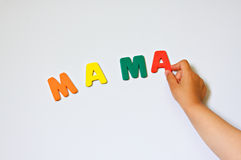 Child hand writing word Mama. On the magnet white-board Stock Image
