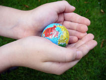 Child handing a globe. Child handing a globe with a grass background, focus on hands royalty free stock photo