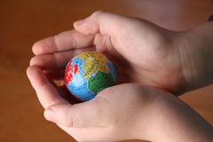 Child handing a globe. Wooden background royalty free stock images
