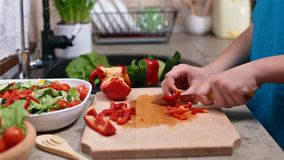 Child hands chopping a red bellpepper - side view. Child hands chopping a red bell pepper for a vegetables salad - side view of the cutting board at the kitchen stock video