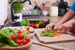 Child hands chopping vegetables on cutting board - the lettuce l Stock Photography