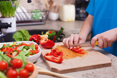 Child hands chopping vegetables on cutting board - the red bellp Royalty Free Stock Image