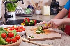 Child hands chopping vegetables on cutting board - slicing the c Royalty Free Stock Photography