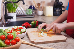 Child hands chopping vegetables on cutting board - the spring on Stock Images