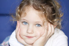 Child with hands cupped on face. A caucasian young child lying on stomach with her hands cupped in her face looking pensive Stock Photography