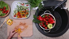 Child hands cutting a bellpepper for a vegetables salad stock footage