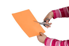 Child hands cutting a paper Stock Images